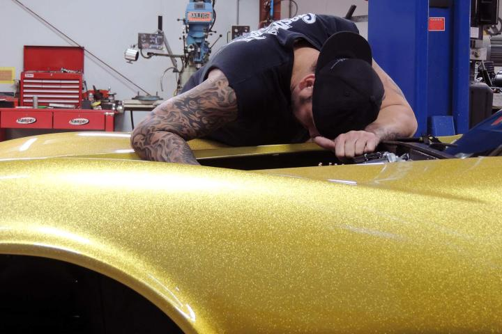 Charles Cimino reaches into the bowels of the 1968 Gold Corvette.