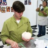 Cake decorator Sonny Robinson works on the head of what will become a