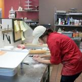 A cake decorator at Caked Las Vegas preparing sushi pieces made of cak