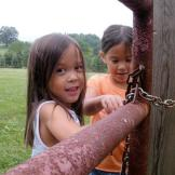 Alexis and Hannah help and lock the gate by the chicken coop.