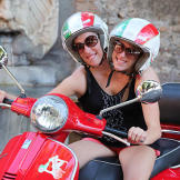 Abby & Brittany try out a Vespa on a scooter tour in Rome.