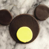 Add two brown fondant circles with diameters of approximately 1 1/2 in