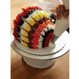 When you've finished feathering your frosting, use white buttercream to create the turkey's beak. Pull up and out from the bottom front of the cake to make the beak.