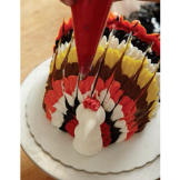 Using the red buttercream, pipe a comb on top of the turkey's head.
