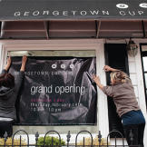 Katherine and Sophie hang a banner just before their grand opening on
