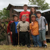 The Roloff Family posing together in front of the farm's saw mill (com