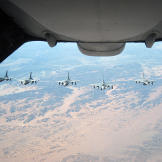Six F-16 Fighting Falcons wait their turn to be administered fuel from