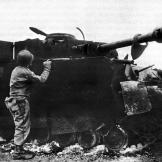 "1944 - A wrecked German tank. Notice its ""Bazooka Pants,"" meant as a defense against rockets.  Watch video of the"
