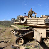 "A tank being ""short tracked"" in 2005. This is usually only done when the tracks and/or wheels have been damaged and no recovery vehicle is nearby. This allows a vehicle with partial running gear to move under its own power. Watch video of the"
