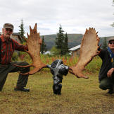 Atz Kilcher and Atz Lee Kilcher kneel aside the moose rack, which they