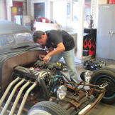 Jeff Thisted works on the engine of a Rat Rod - a style of hot rod tha