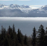 Thick fog hangs over the far side of the bay and snow capped mountains.