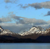 Mountians hovering over the waterline of the bay, as thick clouds move in from a fjord in the distance.[/br[