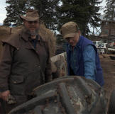 Otto and Shane stands near a tractor and inspect the tires beofre head