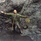 "John shows off his first dig at the Big Nugget Mine in 1984. After his ""retirement"" a couple of years earlier, John got into gold mining almost full-time. The pit he's standing in is the result of two years of digging to reach bedrock … but there wasn't a flake of gold to be found!"