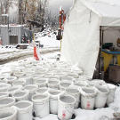 "Buckets of ""pay dirt"" — topped off with icy slush after a freeze — await final refinement outside the processing tent that contains wave tables, pans and a variety of experimental machines all designed to separate black sand from gold. In a final pass at recovering as much gold as possible, the remaining dirt is all manually panned."