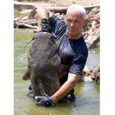 Jeremy Wade holds a flathead catfish he pulled from its underwater lai