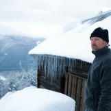 Les Stroud in front of a modest shelter in the extremely cold Norwegia