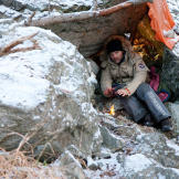 Les Stroud tries to keep warm under a makeshift shelter in the mountains.