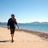 Les Stroud walks on a beach on Tiburon Island looking for items to salvage.
