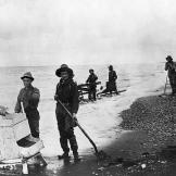 Miners with simple shakers and box sluices work the beaches that are s