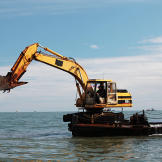 The barge's excavator crane extends out to dig up bottom sediment. A c