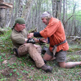 Cody uses moss and wilderness medical skills to dress Dave's wound tha