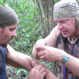 Cody uses ant pinchers to seal Joe's wound on their survival mission i