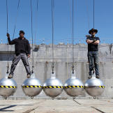 Jamie Hyneman and Adam Savage perch atop giant steel balls. (We'll spa
