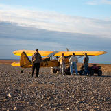 A pilot helps passengers unload at the Kavik River Camp, a remote northern settlement not far from Deadhorse, Alaska.