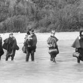A group of actresses crosses the Dyea River in Alaska heading for one of the new boom towns. The larger settlements featured theaters that usually played to large male audiences hungry for entertainment.