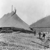 Miners stand next to a massive tailings pile in the heart of the Klondike gold fields. Moving and disposing of massive spoil piles demanded considerable time and labor.