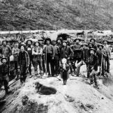 A group of miners employed by one of the Klondike's major claim holders pose with a young girl and a dog. Several years after the beginning of the gold rush, thousands of small claims were consolidated into fewer larger claims that could marshal the resources for mass processing and have some hope of turning a profit.