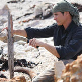 In Tasmania, Mykel uses a heavy rock as an assist while he splits a very hard piece of driftwood with his knife. Using even primitive tools, like this stone employed as a hammer, can save a lot of physical energy. Minimizing caloric expenditure is crucial when intake of food and water is so low.