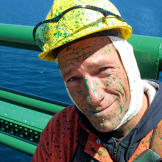Mike Rowe helps maintain the Mackinac Bridge, which included giving it — and his face — a fresh coat of green paint.