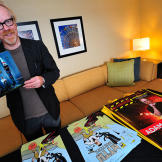 Adam Savage, flanked by the limited-edition posters and bags he autogr