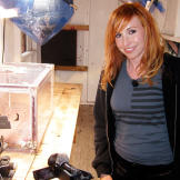 """Kari Byron poses with the """"Gas Room Boom"""" scale model."""