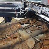 The Cadillac is in a severe state of disrepair. The floor panels will