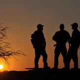 Rob (Navy SEAL ret.), Saw (Navy SEAL fmr.), Biggs (Navy SEAL fmr.), Oz (Green Beret) standing on Reva vehicle at dusk.