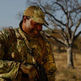 Oz (Green Beret) sharing a moment with an opharned rhino calf.