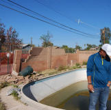 John Ray assesses the condition of the pool and back yard at this property in Phoenix.