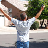 Ed Rosenberg raises his arms in triumph after winning a house.