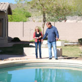 Doug Hopkins and Shari Pozniak admire the finished swimming pool at this property. How much value does a swimming pool add to a home? Watch Property Wars to find out!