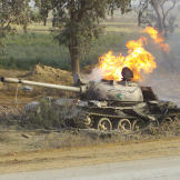 Still in flames, a destroyed Chinese-made Type 69 Main Battle Tank (MBT) north of the An Nu'maniyah bridge on Highway 27, during Operation Iraqi Freedom, April 2003. Watch video of the