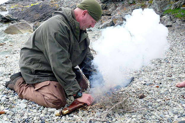 Dave shows how to get a fire going with the sparking percussion action of a black powder rifle.